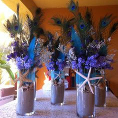 thinner vases, subtract the actual feathers, add orchids in the vase and lotuses around the table.  i love the shells and the colors though