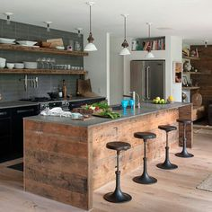 Wide reclaimed wooden boards in Island with cut out sink and industrial style stools