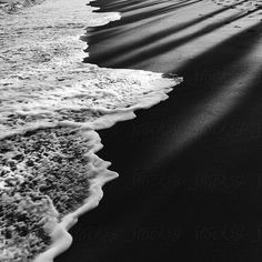 Srdjan Kirtic for Stocksy United - Black and white photo of a black sand beach detail; waves washing ashore with palm tree shadows over the sand.  ashore, background, beach, black, black and white, black sand, cast, coast, contrast, copyspace, day, daylight, detail, diagonal, foam, holiday, landscape, light, line, minimal, minimalistic, monochrome, natural, nature, nobody, ocean, outdoor, outside, retreat, sand, sea, seascape, shadow, shore, sri lanka, summer, summertime, texture, vacation…