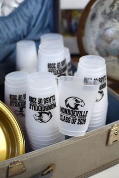 Reusable frosted cups personalized with the graduate's school mascot design, name and 'Class Of' year or graduation date make useful graduation party decorations and double as souvenirs guests can take home to use again and again. Use them at your graduation drink station for guests to help themselves. These graduation cups can be ordered at http://www.tippytoad.com/16-oz-frosted-plastic-school-mascot-cups.asp