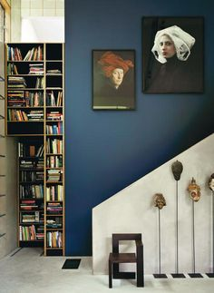 Le bleu Vermeer et les portraits inspirés de ceux des peintres hollandais du XVIIe siècle font écho à la collection de masques primitifs. Chaise Steltman, de Gerrit Rietveld, designer néerlandais majeur de la génération Mondrian et du mouvement artistique De Stijl. Derrière, la bibliothèque coulisse et ouvre sur la chambre.