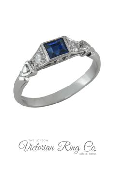This unusual Art Deco style sapphire ring is set with a square central gemstone. The sapphire is highlighted by a diamond on either side, leading to a romantic heart motif. This ring is part of our exclusive Art Deco rings collection. Each ring is true to the original vintage jewellery design. #sappphirering #sapphireengagementring #bluesapphire #artdecoengagementring #heartmotifring