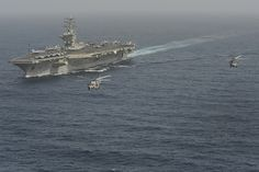 """GULF OF OMAN (June 21, 2013) Two MH-60R Sea Hawk helicopters assigned to the """"Wolf Pack"""" of Helicopter Maritime Strike Squadron (HSM) 75 fly past the aircraft carrier USS Nimitz (CVN 68). Nimitz Strike Group is deployed to the U.S. 5th Fleet area of responsibility conducting maritime security operations, theater security cooperation efforts and support missions for Operation Enduring Freedom"""