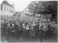 Elever i skolegården Giersings R. En mængde elever opstillet i skole- gården Giersing Realskole opstillet til foto. Til højre under lindetræet ses skolebestyrer F.C.N Vesterdal og som den høje mand skoleinspektør Chr.M.K . Petersen. 1918