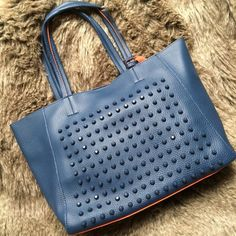 """Blue/orange studded faux leather 3-in-1 tote bag This 3-in-1 tote is a faux leather material, studded on one side, two-tone colors. Two small coordinating bags, one coin purse sized, one cross-body sized with removable strap. Direct from vendor, does have some manufacturing imperfections on the inside, see picture. Snap closure on large bag, zipper closures on small bags.  L(H:10"""", W:17"""", D:6""""), M(H:8.5"""", W:10"""", D:2.5""""), S(H:5.5"""", W:7.25"""") NO TAGS. Bags Totes"""