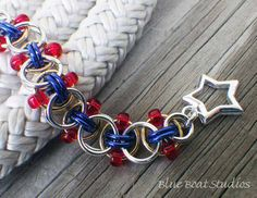 This beaded chain maille bracelet combines silver and blue anodized aluminum jump rings with red beads and a subtle touch of brass for a crisp,