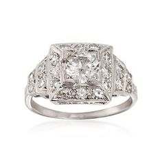 C. 1990. This gorgeous 1.20 ct. t.w. certified diamond ring features a principal GIA certified round brilliant cut diamond of .70 carats in a square mount with near-colorless round diamonds which also descend step-style on the shoulders. GIA cert #6157199015. Textured and polished platinum ring.  <b>Exclusive, one-of-a-kind Estate Jewelry.</b> Free shipping & easy 30-day returns. Fabulous jewelry. Great prices. Since 1952.
