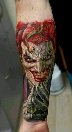 Joker tattoo by Dmitriy Samohin, evil jester, grin, clown, skull, arm wrist tattoo