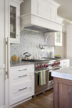 Drawers instead of cabinets next to stove/oven.  hood detail and amazing backsplash