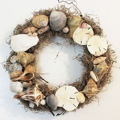 Use a hot glue gun to attach your shell collection to a wreath and display it on a garden fence. These gorgeous wreaths will last for years and are naturally weather safe! More seashell craft ideas in this post. #ad #seashells #wedding