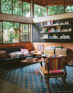 Com vista para o verde, essa sala de estar tem móveis com cara de antiguinhos, parede de lousa e  piso de hidráulicos.