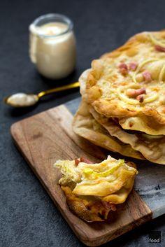 Przepis na alzackie podpłomyki: tarte flambée, zwane również flammkuchen, podawane z crème fraîche, boczkiem i cebulą. Idealna przekąsa do piwa lub wina.
