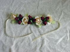 Bun Wrap, Floral Bun Wrap for Ballet, Skating, Bridal Whitney by Ribbons and Roses Boutique. $9.99. This handmade, one of a kind hair bun enhancement is adorned with Ivory  roses, as well as Burgundy rosebuds.  A 12 inch feather edged ribbon has been added on each end of the floral strip so that it can be tied either in front or in back of your hair bun.  The floral strip measures approximately 8 inches and is designed with a wire armature so that is can fit around any size ...