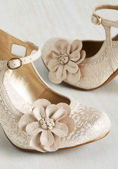 Let your imagination scamper freely while your ensemble joins along with these unique heels! Whimsical and wonderful, these ivory and metallic champagne Mary Janes flaunt scalloped seaming, triangular cutouts, brocade accents, and a beautiful flower applique that turn your frolic into a flight of fancy!