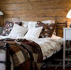 Decorate your bedroom for Fall. Pillows and a plaid in Autumn colors combined with a reclaimed wood headboard give this bedroom a 'cabin in the woods' feel. hppt://www.songbirdblog.com