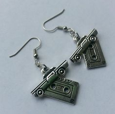 These earrings were inspired by Dean Winchester from Supernatural. They feature silver cassette tape charms, as well as silver impala charms. The ear hooks are lead/nickel free. Earrings come with rub