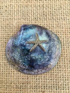 """This one of a kind shell makes a great addition to your shell collection! Or a wonderful gift for yourself or a friend! It measures 2 1/8"""" wide x 2 """" high It has been adorned with alcohol ink and glitter and a metal starfish to created this unique design! This is from a self Painted Sand Dollars, Alcohol Ink Jewelry, Shell Collection, Starfish, Shells, Gemstone Rings, Glitter, Brooch, Gemstones"""
