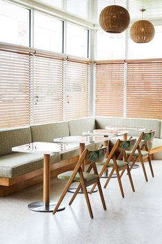 A Revived Midcentury Motel in New Orleans With Serious Flair - Photo 4 of 11 - A built-in banquette with light green, tweed patterning is paired with tropical, wooden folding chairs.