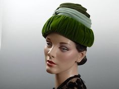 Late 1950s womens hat draped green velvet turban with a tall crown and faux pearl trim. In the late 1950s hats were designed with taller crowns to accommodate the full bouffant hair styles. The layered velvet is in 3 different shades of green: dark forest green, mint green and a dark chartreuse. Vintage condition is good with very minor signs of age or use. The velvet has some thinning to the edges but no holes and union tag is crumpled (refer to last photo). I measured 21.5 inches around…