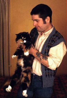 Ozzy Osbourne with a cat. forget the damn cat, what is up with that doofus sweater and short hair??!! I dont know that Ive seen him with short hair before....it is easy to see how much Ozzy loves all animals, though. he is a teddy bear inside