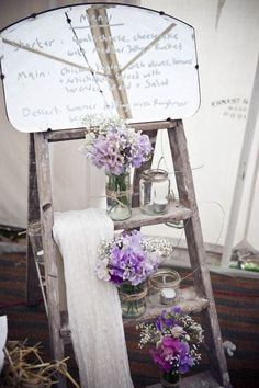 Wedding menu written in white on an antique mirror & vintage inspired props with purple flowers...
