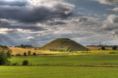 Silbury Hill    Silbury Hill is a prehistoric artificial chalk mound near Avebury in the English county of Wiltshire. It is part of the Stonehenge, Avebury and Associated Sites UNESCO World Heritage Site.At 40 metres high, Silbury Hill – which is part of the complex of Neolithic monuments around Avebury, which includes the Avebury Ring and West Kennet Long Barrow – is the tallest prehistoric human-made mound in Europe and one of the largest in the world. (from wikipedia.org)