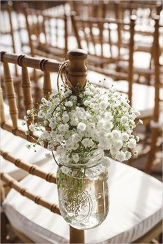 Simple but hanging on shepards  hooks with colored flowers while burlap and baby's breath from the back of the chairs?