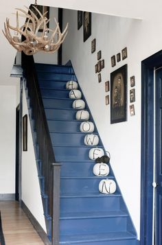 Acrylic paintings by Russian artist Nina Friday line the stairwell of this Vermont home, where the steps are painted Sherwin-Williams's Naval.   - CountryLiving.com
