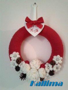 Ghirlanda in base di polistirolo, ricoperta con nastro in iuta rossa e decorata da margherite, rose e boccioli di rose lavorate singolarmente a mano all'uncinetto e completate da pigne e ghiande decorative.