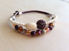 Pearl and bronzed colored stretch bracelet with brown leather.  by Amy Morais