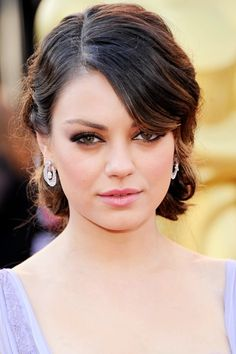 """""""I wanted to recall old-Hollywood glamour—soft and feminine,"""" says Roszak about the side-parted updo she crafted for Mila Kunis. After curling sections with a one-inch-barrel curling iron, Roszak used her fingers to separate and pin waves at the nape of the neck."""