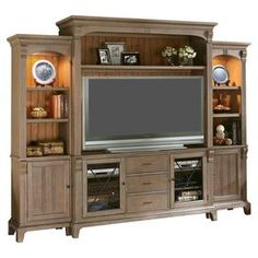 Add country-chic appeal to your living room or den with this rustic entertainment center, showcasing 4 cabinets and 2 storage towers for displaying family photos and vibrant decor.  Product: 1 Media console, 1 hutch and 2 cabinetsConstruction Material: Hardwood solids, oak veneers and glassColor: Shenandoah barnwoodFeatures:  Four doorsTwo drawersRemovable top molding accents Tip restraining hardware Three open compartments Turned feet Touch-switch lightingSix adjustable shelvesDrawers have…