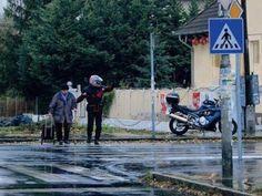 Un motociclista che si ferma per aiutare un'anziana ad attraversare la strada
