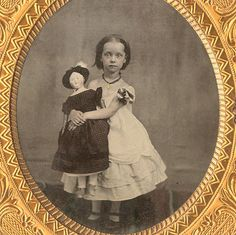 An endearing view of a fancily-dressed girl and her large, equally fancy doll.