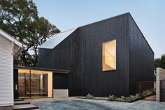 Modern Texan addition and renovation facade with cypress paneling and metal roof