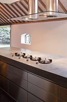 Maatwerk keuken. RVS fronten. Betonnen blad, inclusief doorlopende betonnen zijwanden. Kookpitten direct vanuit het blad.