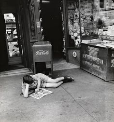 Photo by John Albok - Boy reading comics in front of newspaper store, west side of Madison Avenue between 96th and 97th Streets.