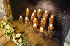 Great way to dress up a non-working fire place, tall cut wood logs at varying heights topped with candles | North Carolina Mountain Wedding At Claxton Farm | Photograph by Jen Yuson Photography  http://storyboardwedding.com/north-carolina-mountain-wedding-claxton-farm/