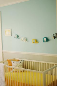 Love the white crib and bright yellow mattress/blanket cover. Elephant wall hanging is cute too but swap in MONSTERS!