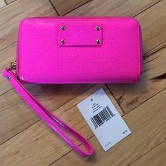 """NWT PINK KATE SPADE WRISTLET WALLET Christmas gift that I know I will never use. The plastic tag holder broke but I still have the tag!! PVC body with perforated spade detailing all over. Main zip closure, signature designer logo label at front, pale gold tone hardware, wrist strap pull and a back slip compartment. Interior: PU and fabric lining with 1 roomy compartment for notes, 4 multifunctional long slots Gold foiled embossed signature designer logo lettering on lining. 7"""" x 3"""" x 1""""…"""