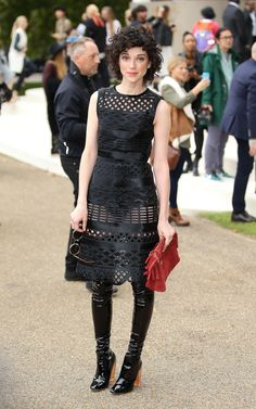 St. Vincent in a black cutout Burberry dress and thigh-high patent black boots