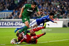 Raul Bobadilla of Augsburg is challenged by Ralf Fahrmann of Schalke 04 and Atsuto Uchida of...