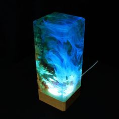 A beautiful unique piece of decor featuring a mesmerizing underwater scene inside. The solid wood base has an LED light inserted, which lights up the entire piece and transforms it into an eye-catching night light. Made with naturally formed burl wood and high quality transparent resin.