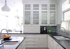 Glass front upper cabinets, white kitchen, dark counters, reeded glass cabinet doors subway tile backsplash. http://cococozy.com