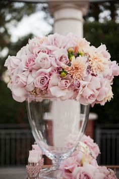 I know these aren't your colors/flowers but the idea of the flowers on top of the vase... beautiful! Would help to reflect light from (any) candles and break up dark tablecloths! -JM