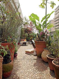 A varanda em L contorna parte do apartamento do diretor de arte de cinema Thiago Bastos. O piso de pedras original foi mantido. Sobre ele, muitas plantas em vasos, bancos e elementos de jardim de vovó, como o cogumelo de cerâmica
