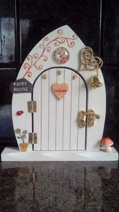 3 different wooden fairy doors with butterfly roses heart
