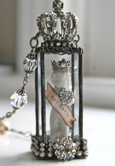 A frozen Charlotte holding an ART SAVES banner encased in soldered glass, topped with a crown and attached to a chain with lovely beads and baubles so carefully and beautifully constructed. An original creation by Shea.