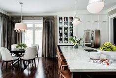 Fabulous open plan kitchen with white ceiling height cabinetry paired with nickel hardware and white marble countertops.