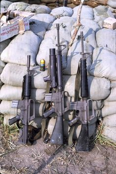 A CAR15 on the far left and two M16s. The center rifle has an attached grenade launcher.